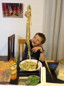 FaceTime is everywhere with us. Here John looks on as Lucas samples  pasta he helped make. © Donatella Lorch