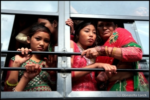 "Women in traditional ""wedding day"" saris are scrunched on buses returning from worshipping at Pashupatinath, a World Heritage Site. ©Donatella Lorch"