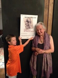 Mina with her grandson Lucas this summer holding up the poster for the launch of her most recent novel ©Donatella Lorch