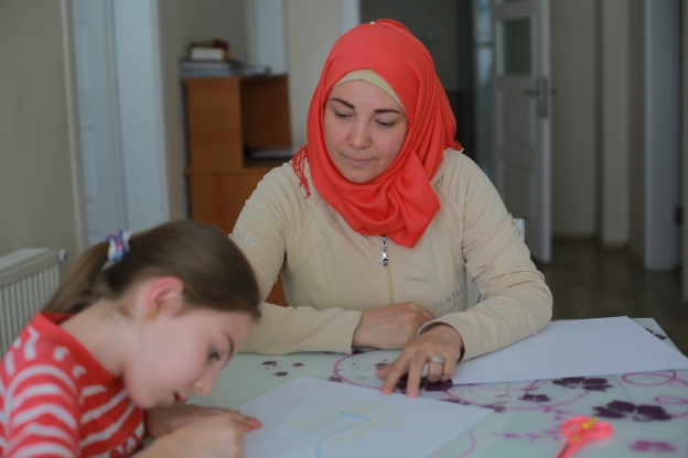 Darie Alikaj, a surian refugee living in Istanbul Turkey helps her daughter Mayas,9, with a drawing. 05:25:16 ©UNHCRDonatella Lorch